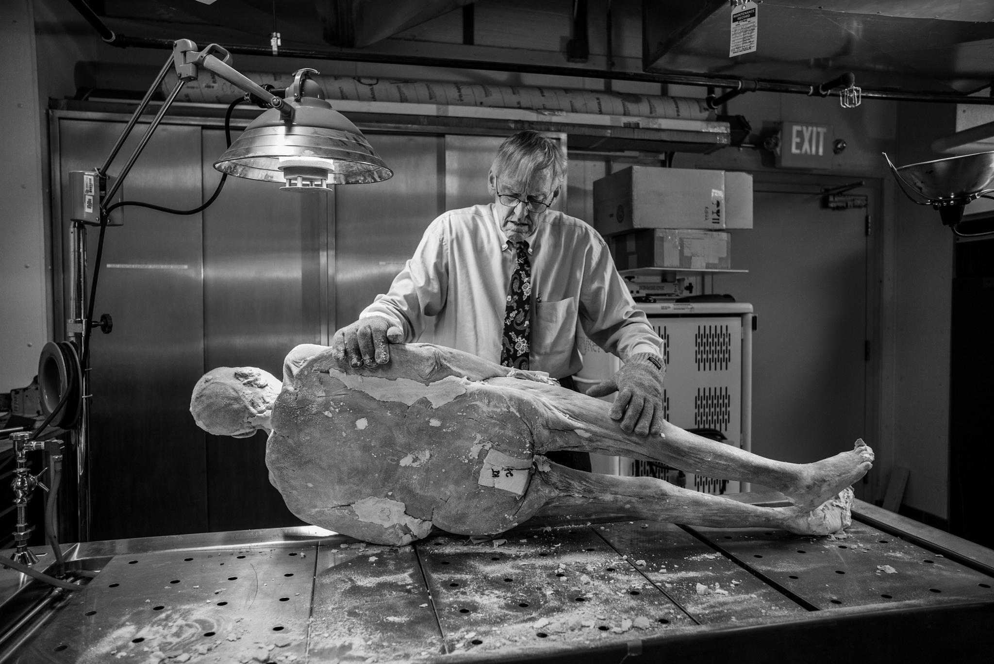 Picture of a man holding a frozen cadaver on its side